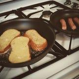 Cottura della prima colazione della salsiccia e del pane inzuppato in latte/uova e zucchero e fritto in padella Immagine Stock