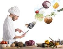 Cottura della ricetta dalla compressa Fotografia Stock