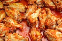 Cottura delle ali di pollo Immagine Stock