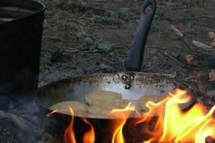 Cottura delle frittelle sul fuoco aperto Fotografia Stock