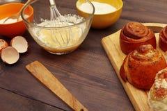 Cottura delle pasticcerie dagli ingredienti ai panini freschi sulla tavola di legno rustica immagine stock libera da diritti