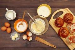 Cottura delle pasticcerie dagli ingredienti ai panini freschi sulla tavola di legno Vista da sopra fotografie stock