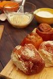 Cottura delle pasticcerie dagli ingredienti naturali ai panini freschi sulla tavola di legno rustica immagini stock libere da diritti