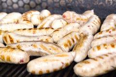 Cottura delle salsiccie sulla griglia Immagini Stock