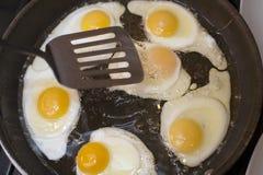 Cottura delle uova fritte Fotografia Stock