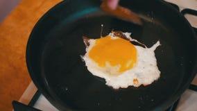 Cottura delle uova in una padella nella cucina domestica stock footage