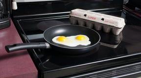 Cottura delle uova in una vaschetta di frittura Fotografia Stock Libera da Diritti