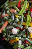 Cottura delle verdure congelate in padella calda Disgelando ed arrostendo la miscela di verdure fotografie stock libere da diritti