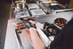 Cottura di tema Le mani si chiudono in su uomo caucasico giovane nei guanti neri del lattice e dell'uniforme in cucina il ristora fotografia stock