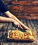 Cottura domestica Le mani del ` s delle donne hanno tagliato la torta casalinga con il riempimento Celebrazione del giorno di ind immagine stock