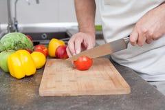 Cottura e concetto domestico - vicini su del pomodoro maschio del taglio manuale sul tagliere con il coltello tagliente fotografie stock
