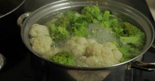 Cottura i broccoli variopinti e del cavolfiore nella pentola con acqua bollente archivi video