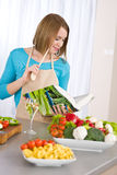 Cottura - libro di cucina della lettura della donna in cucina immagini stock