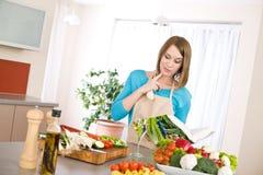 Cottura - libro di cucina della lettura della donna in cucina Fotografia Stock Libera da Diritti
