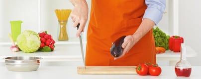 Cottura nel paese Il ` s dell'uomo del primo piano passa le verdure di taglio su una superficie di lavoro in una cucina Fotografie Stock Libere da Diritti