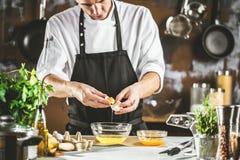 Cottura, professione e concetto della gente - cuoco maschio del cuoco unico che produce alimento alla cucina del ristorante immagine stock libera da diritti