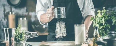 Cottura, professione e concetto della gente - cuoco maschio del cuoco unico che produce alimento alla cucina del ristorante immagine stock