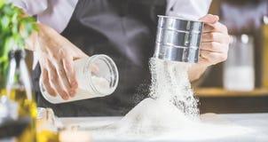 Cottura, professione e concetto della gente - cuoco maschio del cuoco unico che produce alimento alla cucina del ristorante fotografia stock