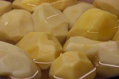 Cottura, pulizia, tagliente e marinante della patata uso di olio e di condimenti incida le fette e cuocia nel forno fotografia stock