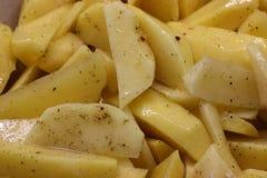 Cottura, pulizia, tagliente e marinante della patata uso di olio e di condimenti incida le fette e cuocia nel forno immagine stock libera da diritti