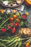 Cottura sana con le verdure organiche fresche Ingredienti e strumenti vegetariani della cucina su fondo rustico scuro, vista supe Fotografia Stock