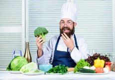 Cottura sana dell'alimento Cuoco barbuto dell'uomo in cucina, culinaria Uomo del cuoco unico in cappello Ricetta segreta di gusto immagine stock