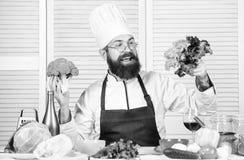 Cottura sana dell'alimento Cuoco barbuto dell'uomo in cucina, culinaria Uomo del cuoco unico in cappello Ricetta segreta di gusto immagini stock