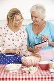 Cottura senior della figlia dell'adulto e della donna nella cucina fotografia stock libera da diritti