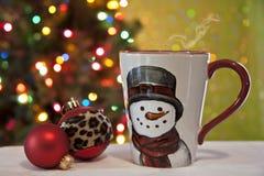Cottura a vapore della bevanda in tazza allegra vicino ad un albero di Natale festivo fotografia stock libera da diritti