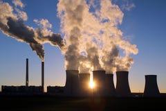 Cottura a vapore delle torri di raffreddamento della centrale elettrica del carbone contro il sole Immagini Stock