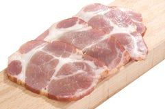 Cou cuit découpé en tranches de porc sur un panneau de découpage Image stock