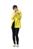 Cou de congélation de bâche de jeune brune de cheveux courts avec le manteau de pluie jaune Photographie stock libre de droits