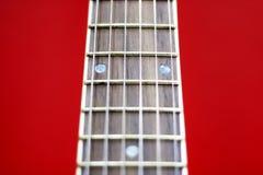 Cou de guitare sur un fond rouge, foyer sélectif en gros plan Photographie stock libre de droits