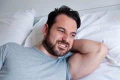 Cou de sentiment d'homme raide après le sommeil dans le lit photographie stock