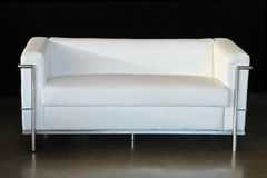 Couch. White leather couch with a black background Royalty Free Stock Image