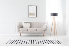 Couch against wall with molding. Beige couch standing against white wall with molding and watercolor poster in cozy living room interior Stock Photos