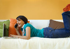 Smiling Woman on Sofa with Phone Royalty Free Stock Photography