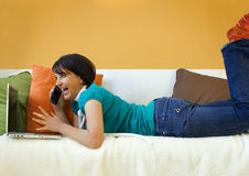 Excited Woman on Sofa with Phone and Laptop Royalty Free Stock Photos
