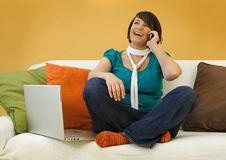 Smiling Woman on Sofa Taling on Phone Stock Image