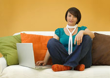 Casual Woman on Sofa with Laptop Stock Image