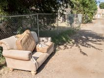 Couch on a city alley way. Discarded sofa on a dirt street Royalty Free Stock Images