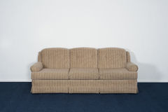 Couch or Davenport, Blue Carpet, Blank White Wall. A couch or davenport, blue carpet, and blank white wall Royalty Free Stock Images