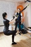 Couch demonstrates exercise. With tourniquet to caucasian woman, who wears electric muscle stimulation suit. Vertical shot Royalty Free Stock Photo