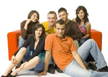Couch full of friends. Group of 6 teenagers sitting on and next to the red couch. They're smiling and looking at camera Royalty Free Stock Photos