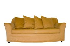 Couch Isolated On White. Picture of a couch with four pillows, in front of an empty white wall Royalty Free Stock Photography
