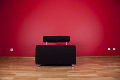 Couch next a red wall Royalty Free Stock Image