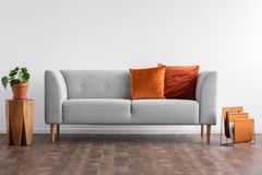Couch with pillows between wooden table and newspaper organizer, real photo with copy space on the empty white. Couch with pillows between wooden table with royalty free stock images