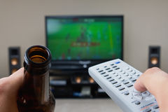 Couch Potato. This image shows a couch potato drinking a beer, and enjoying a program on television Stock Photos