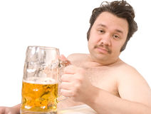 Couch potato. Overweight man sitting on the couch with a beer glass Stock Image