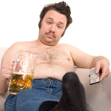 Couch potato. Overweight man sitting on the couch with a beer glass and remote control royalty free stock image
